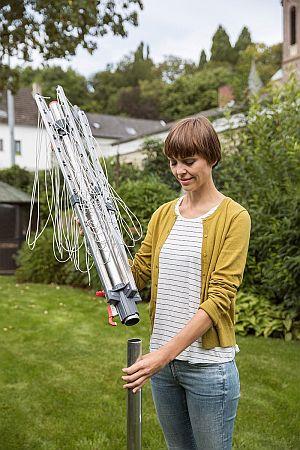 Abbildung: Frau baut Wäschespinne im Garten auf