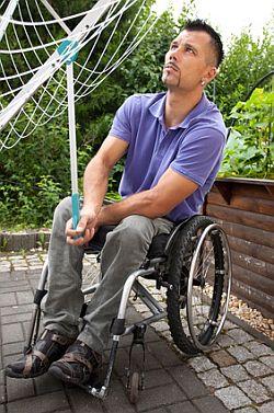 Mann im Rollstuhl öffnet eine Wäschespinne